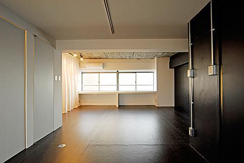 玄関に入り窓の方向を見ると、右側は黒い壁、左側は白い壁と上品なカーテン。