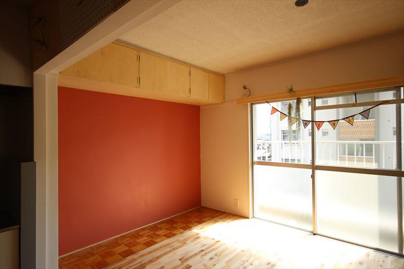 無垢フローリングで仕上げた床とブラッドオレンジのような色で塗装されたリビングの壁